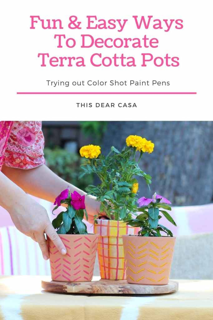 Hands holding and arranging painted terra cotta flower pots on wood tray.