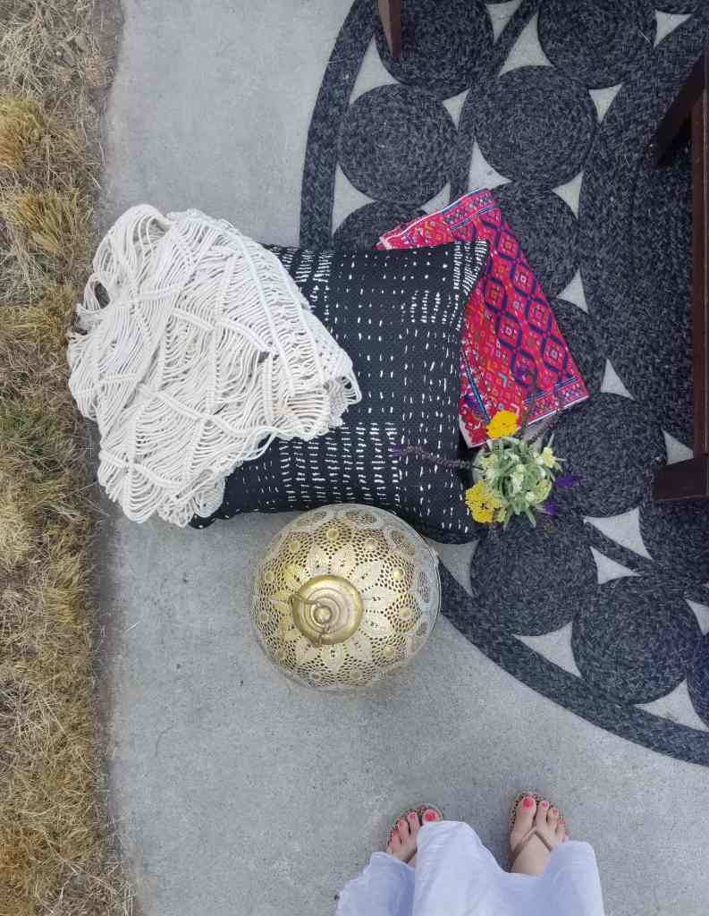 Boho style patio accessories- macrame wall hanging, print pillow, lantern, rug, and embroidered ethnic table runner.