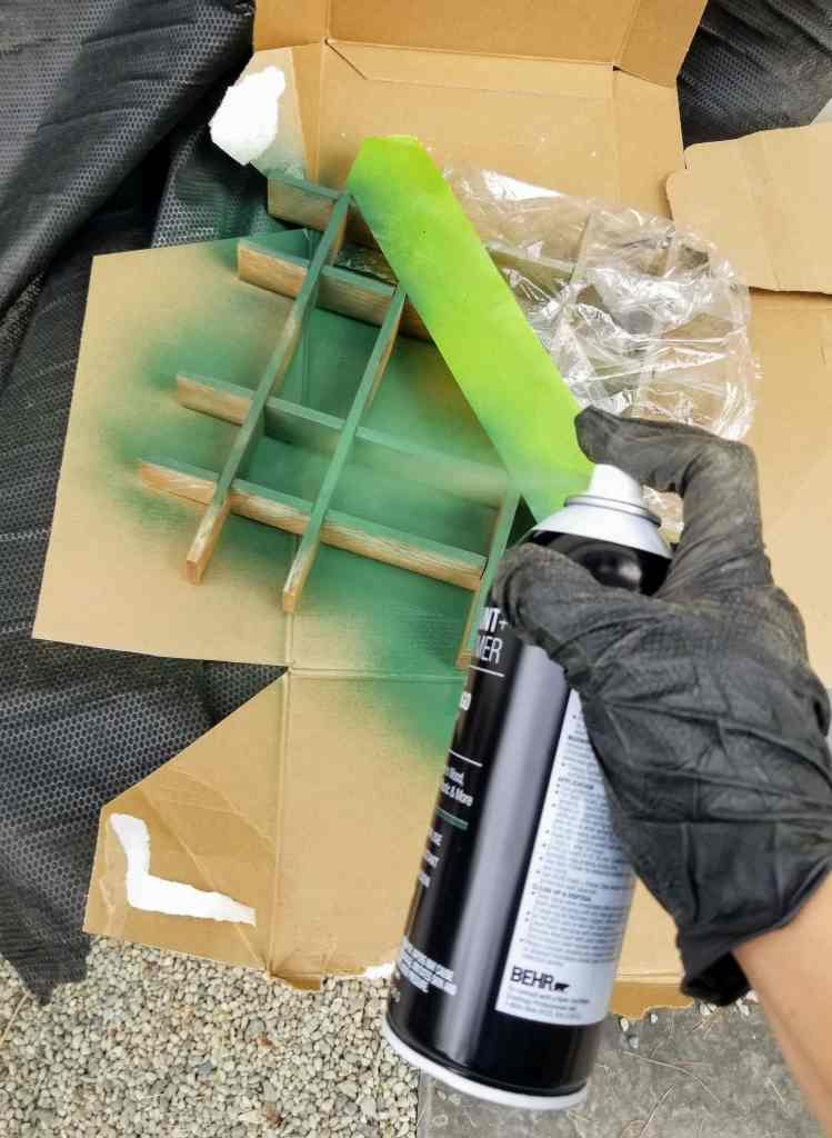 Hand in glove spraying can of spray paint.