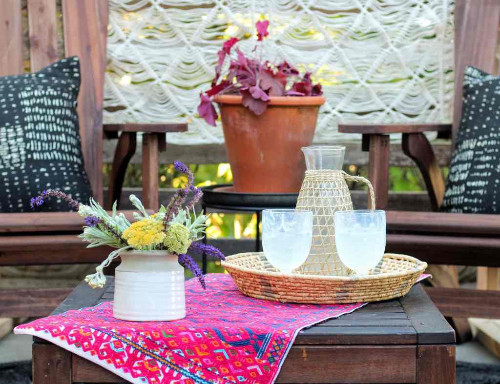 Small patio table with flower arrangement and drinkware.