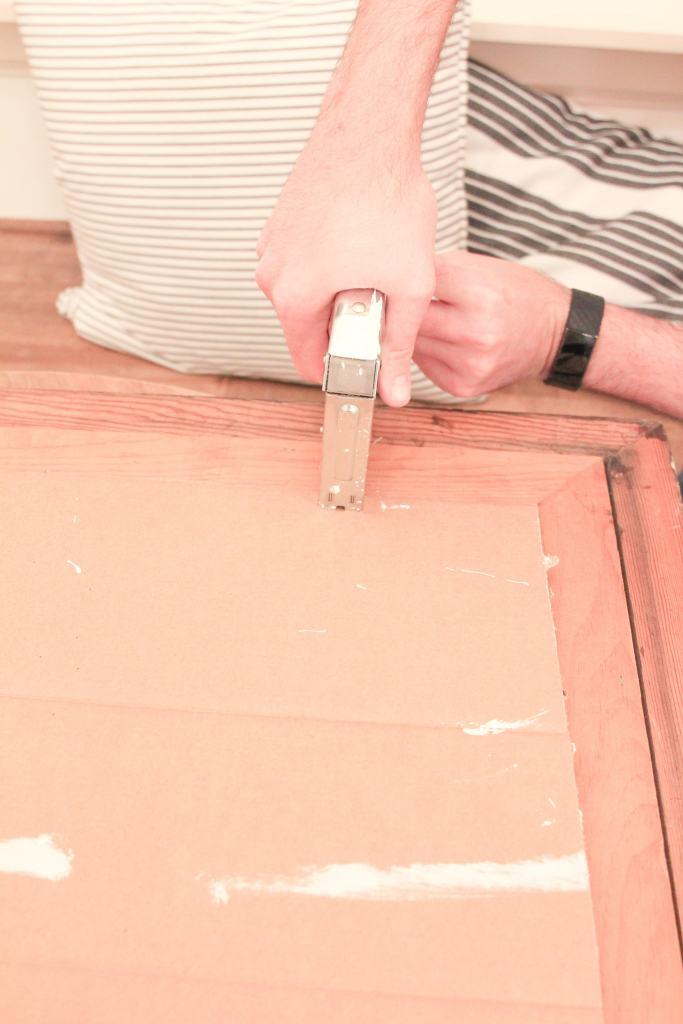 Hand holding staple gun stapling cardboard to wood frame.
