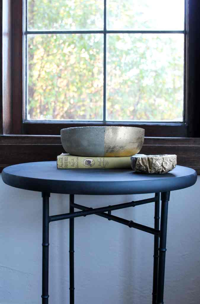 Lead glass window with dark wood frames. Do it yourself concrete bowls on black table.