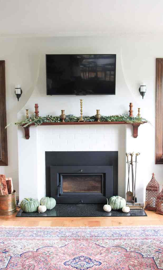 Tudor Revival fireplace with stained wood mantle. Garland and candlesticks on the mantle.
