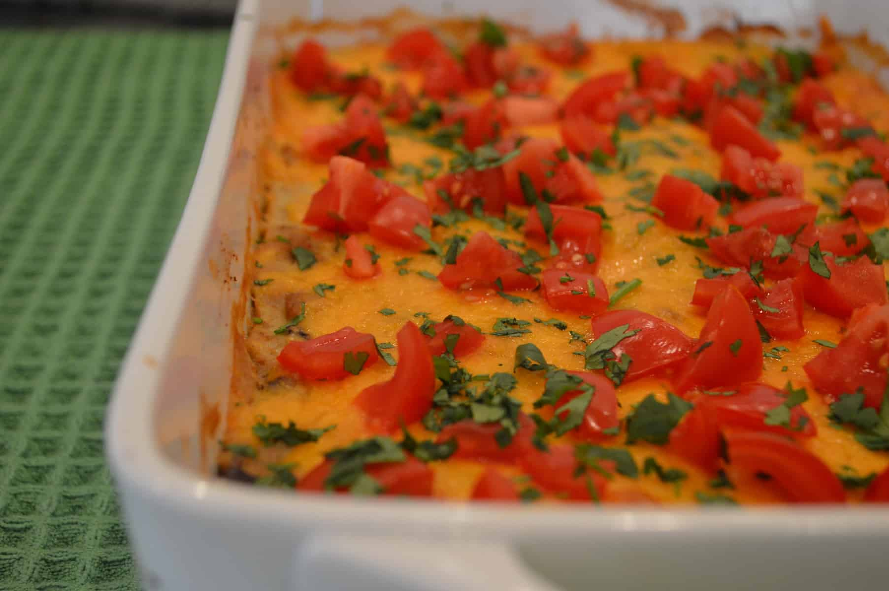 Green Enchilada Casserole in a white baking pan topped with tomatoes and cilantro
