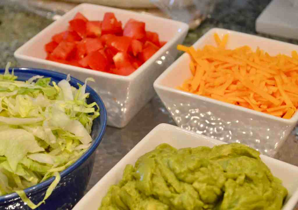 toppings for taco bar include sour cream, guacamole, cheddar and tomatoes