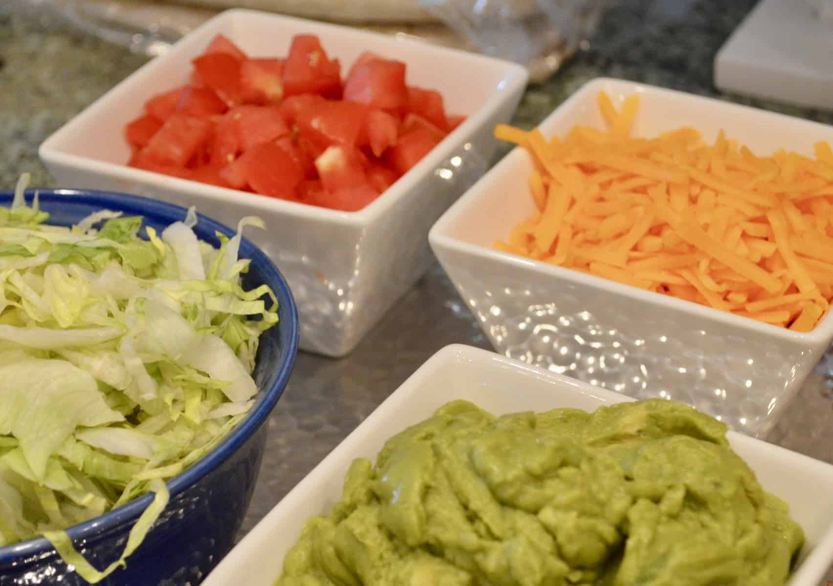 toppings for cream cheese chicken enchiladas include shredded cheese, guacamole, lettuce, tomatoes and sour cream