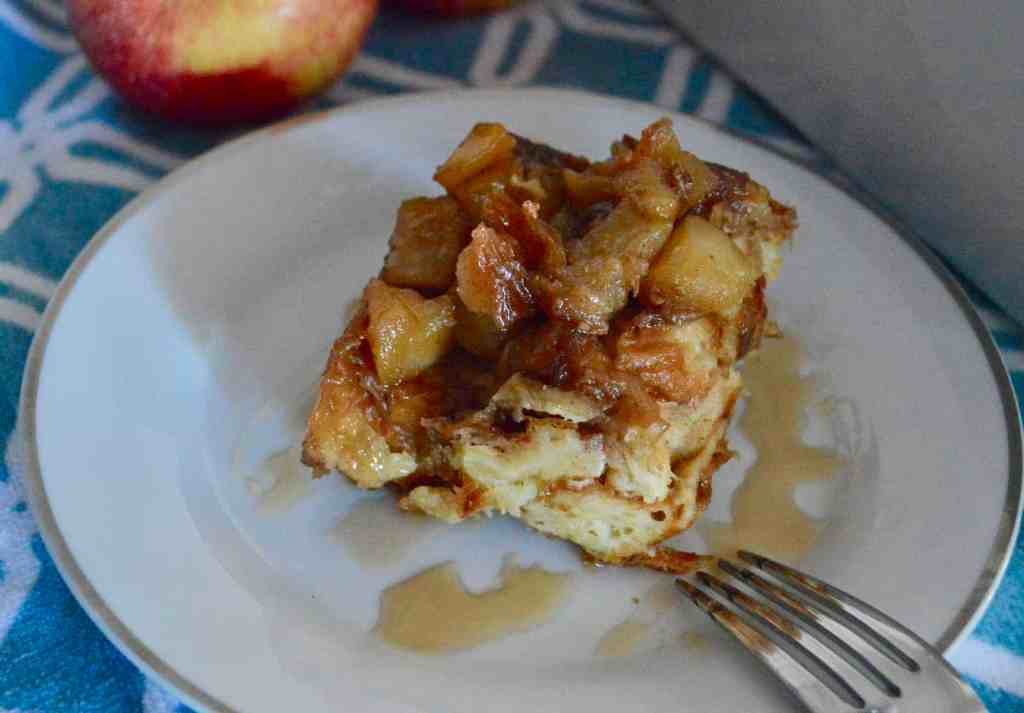 croissant baked French toast with cinnamon apples and warm maple syrup on a white plate