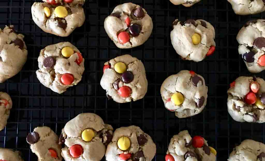 Reese's Pieces Peanut Butter Chocolate Chip Cookies on a wire cooling rack