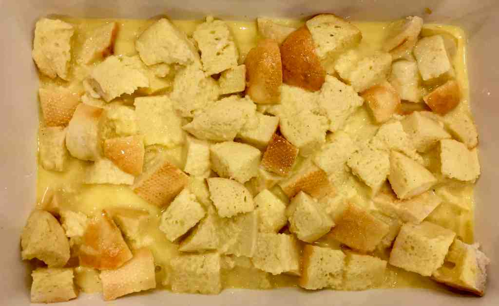 custard poured over the cubed bread in the baking dish.