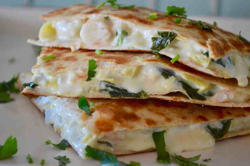 Spinach Artichoke Shrimp Quesadillas on a white plate with cilantro sprinkled over top