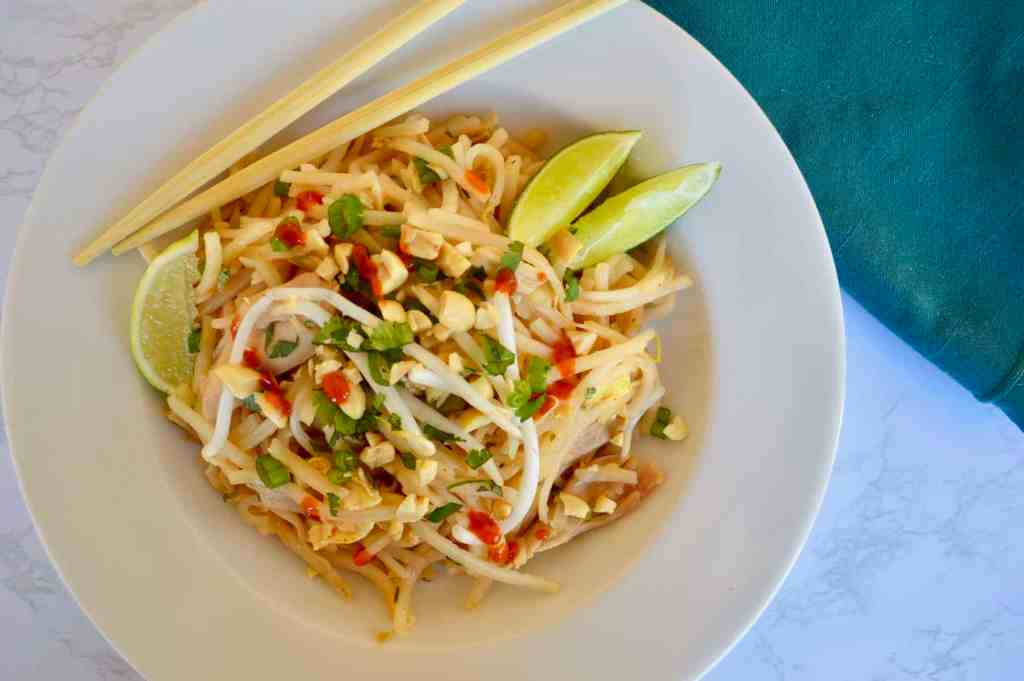 Rotisserie Chicken Pad Thai in a white bowl with lime wedges and chopsticks