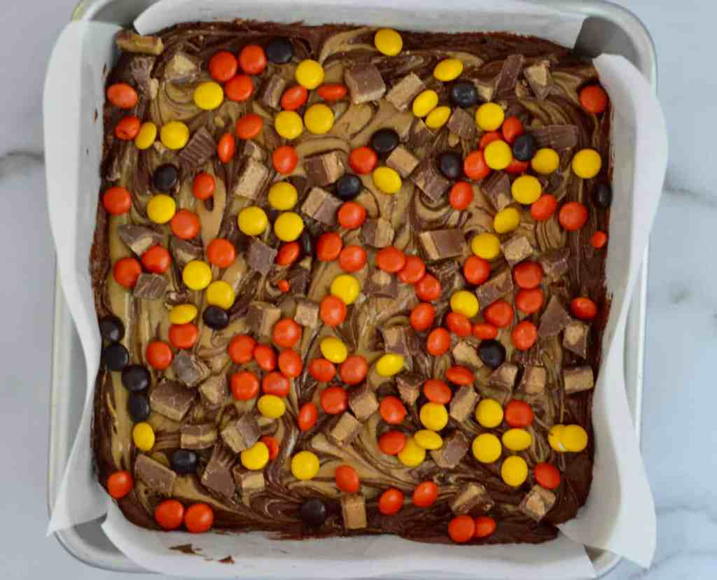 sprinkle the peanut butter cups and Reese's pieces on the brownie peanut butter batter
