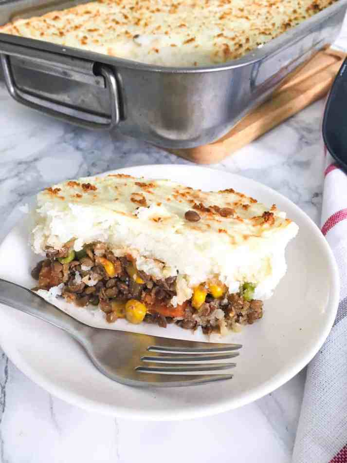 slice of lentil shepherd's pie in plate with fork