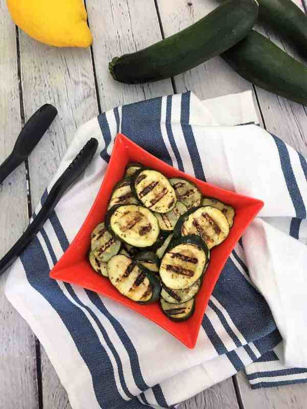 grilled zucchini slices in serving dish with tongs laying beside it
