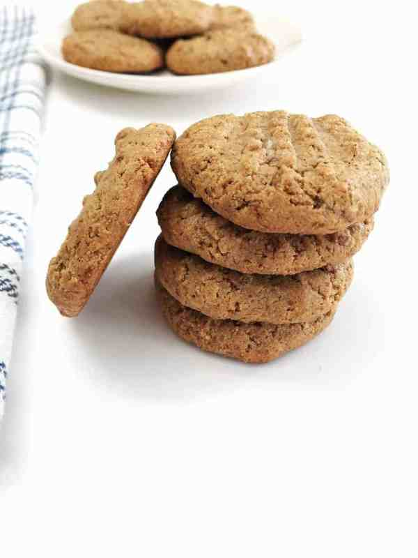 stack of almond butter cookies with cookie leaning on side