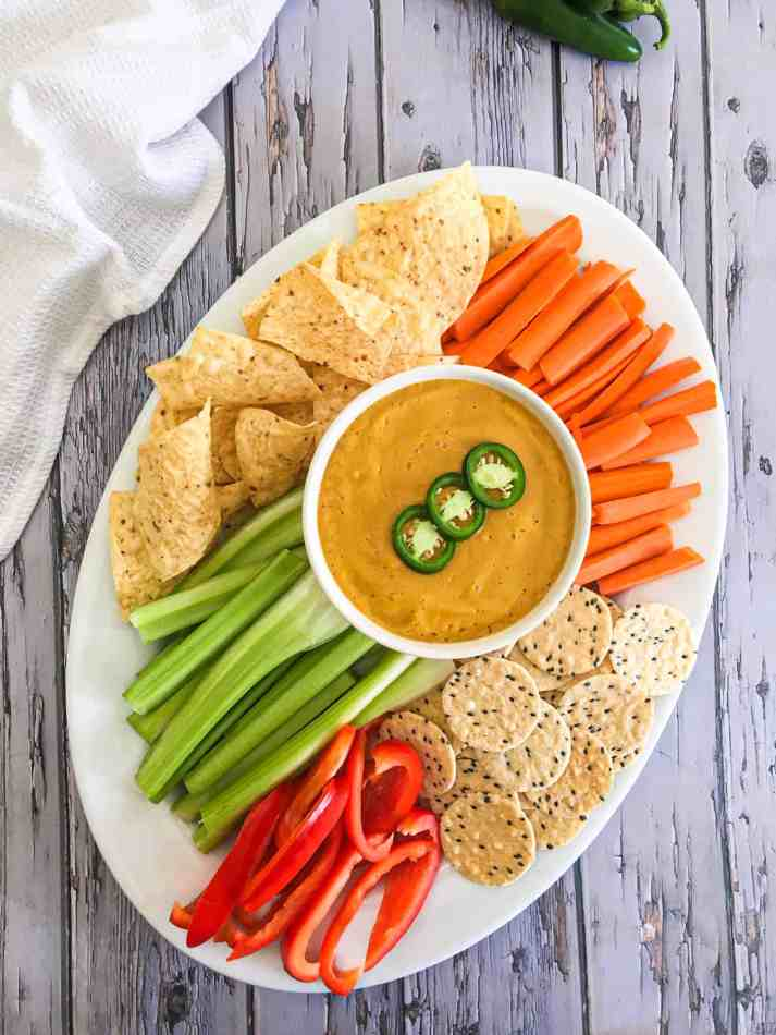 carrots, celery, peppers, crackers and chips in large white tray with dip in the middle