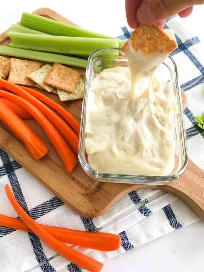 cracker dipping into cheese dip