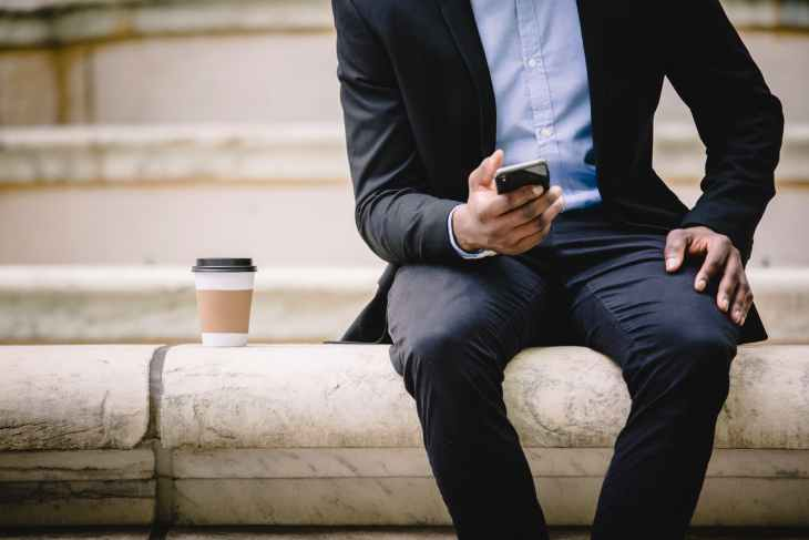crop businessman using smartphone while resting on bench with takeaway coffee