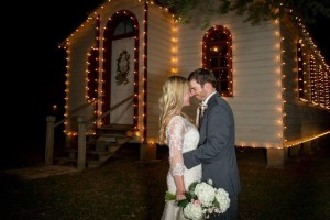 A husband and wife hug each other on their wedding day. They stand in front of a lit up chapel in the evening.