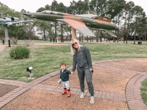 A mom and toddler look at airplanes together.