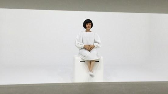 A robot sits on a pedestal behind a wall.