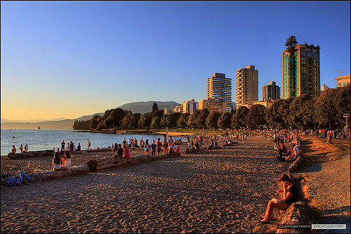 People relaxing on the beach watching the sunset at English Bay