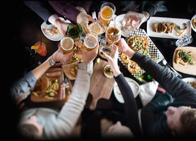 People toasting over drinks and dinner during happy hour in Vancouver