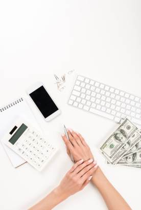 Woman with calculator, money, keyboard, phone, figuring out her finances