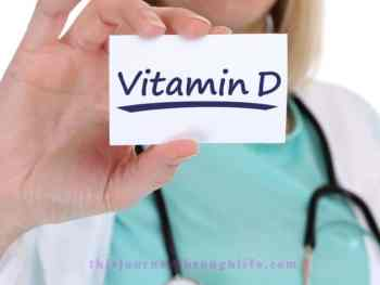 female doctor with stethoscope holding Vitamin D on a card