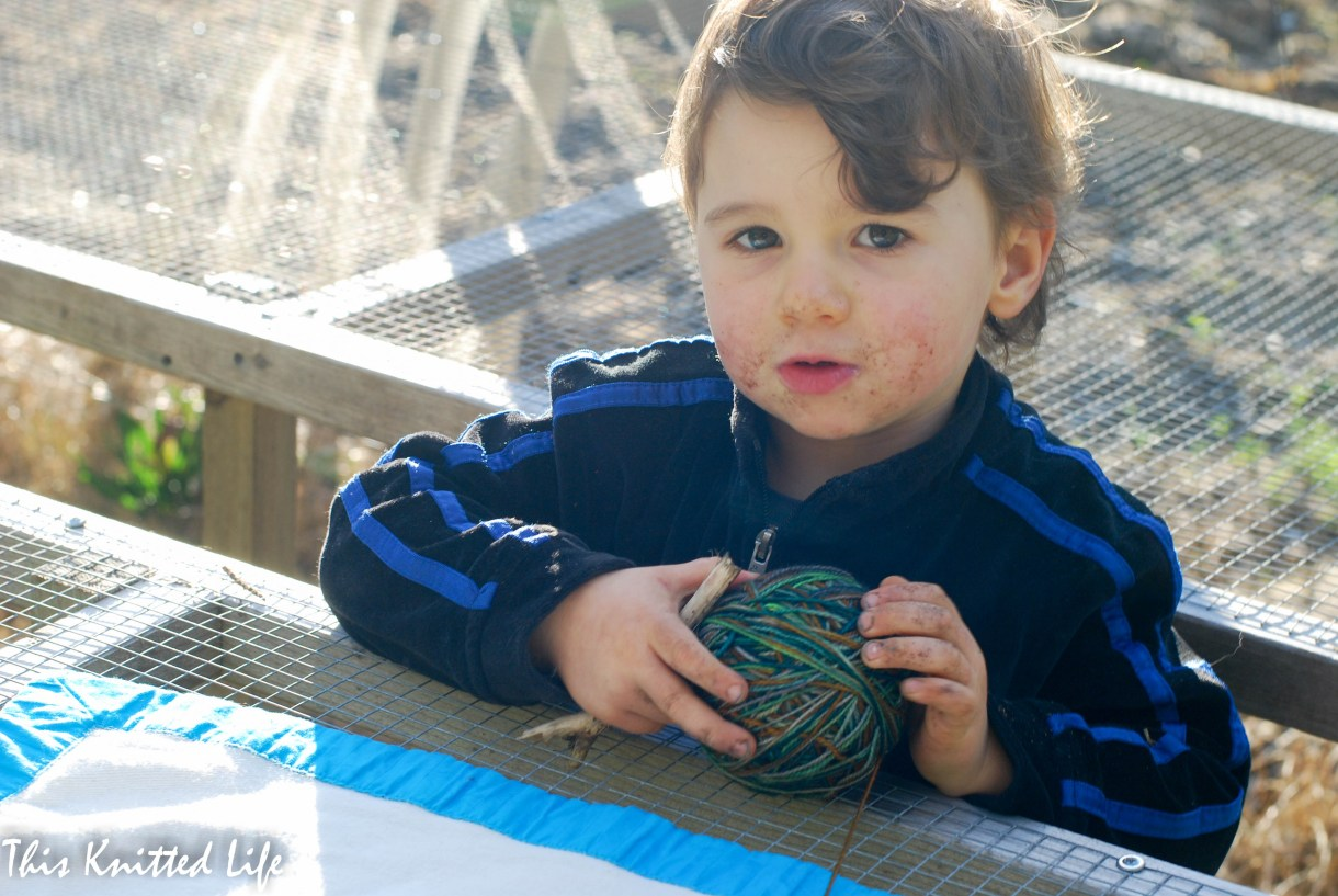 Super cute kid (with a dirty face) holding mom's yarn.