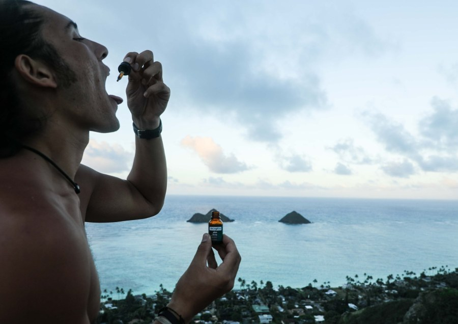 Man taking CBD in front of ocean