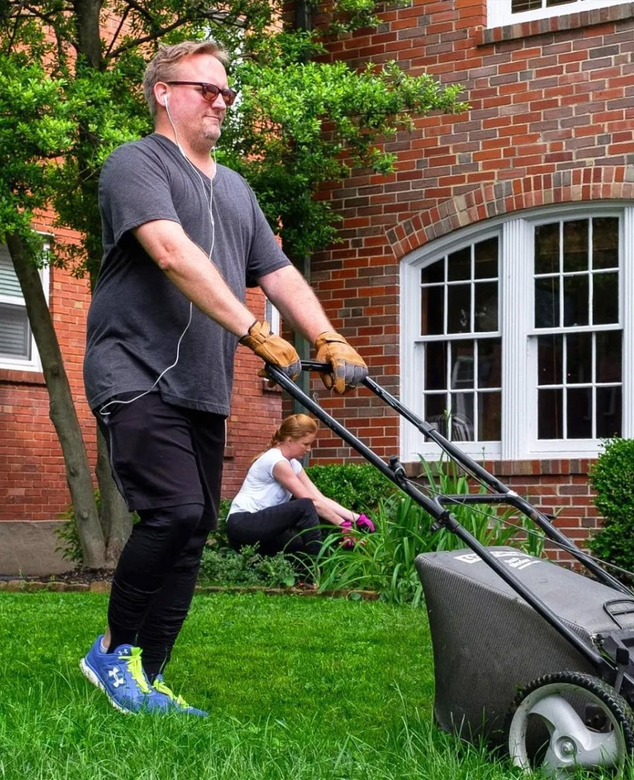 Man mowling lawn with resistance pants on