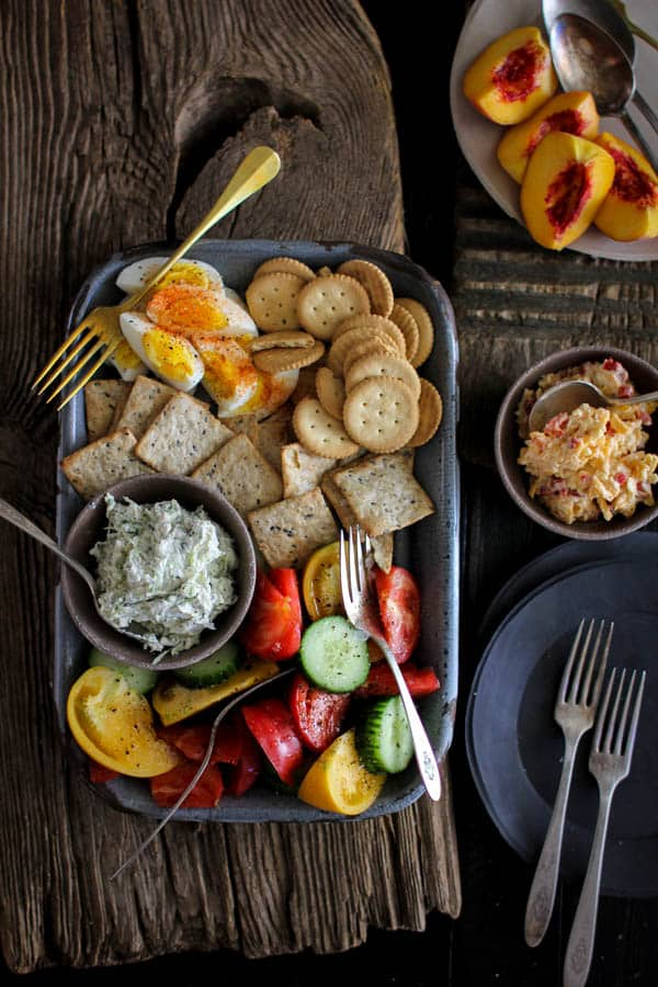 Southern Picnic Platter recipe || This picnic platter transports me back to summers growing up in the south. Homemade pimento cheese, benedictine spread, a juicy heirloom tomato and cucumber salad, fresh peaches, spice dusted hard boiled eggs, and a variety of crackers! My grandmother would have been proud of this one! || @thismessisours