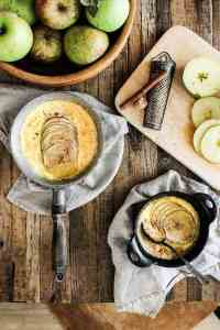 Baked apple custard on table with sliced fresh apples and cinnamon sticks