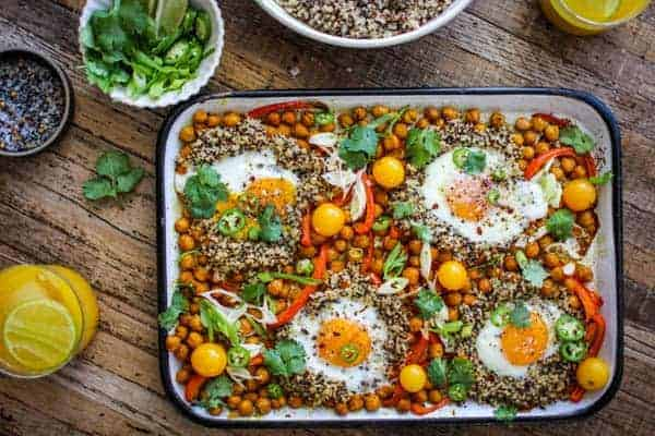Sheet pan full of roasted chickpeas, red bell pepper, and cherry tomatoes with quinoa an perfectly baked sunny side up eggs.