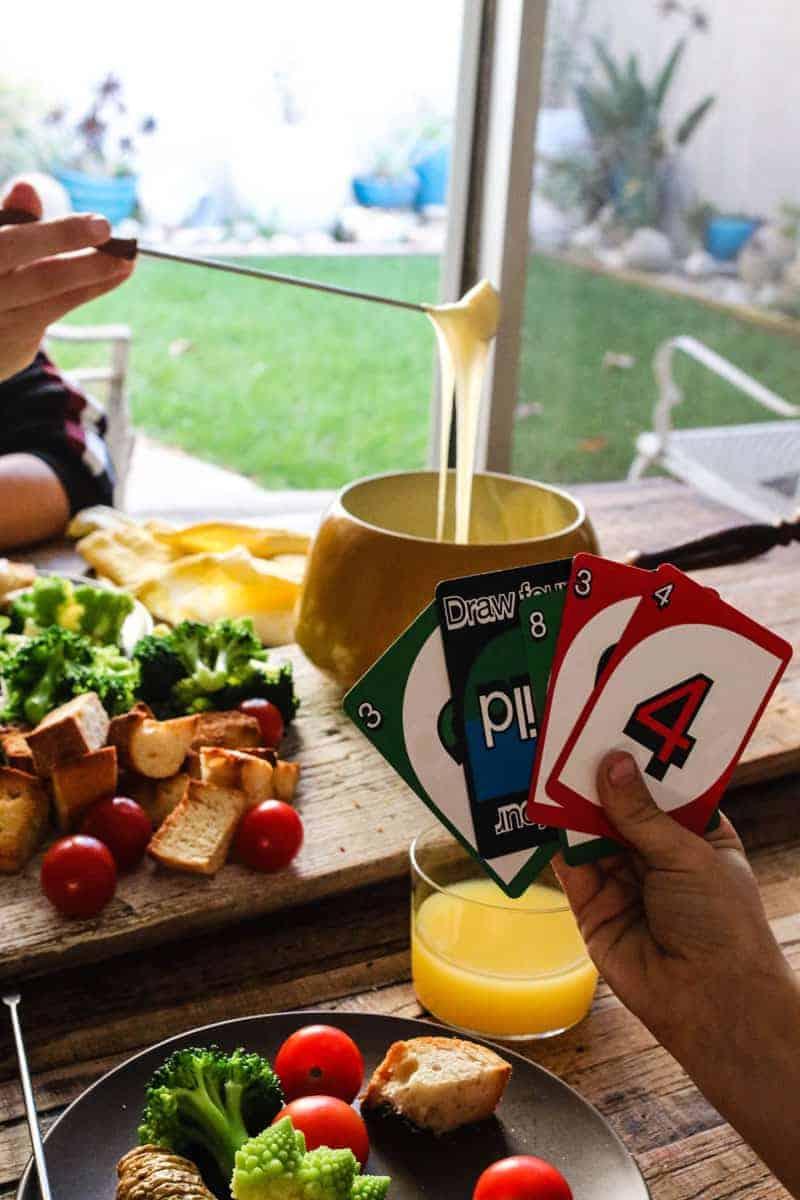 Kids playing Uno, fondue cheese board, girl dipping bread into fondue