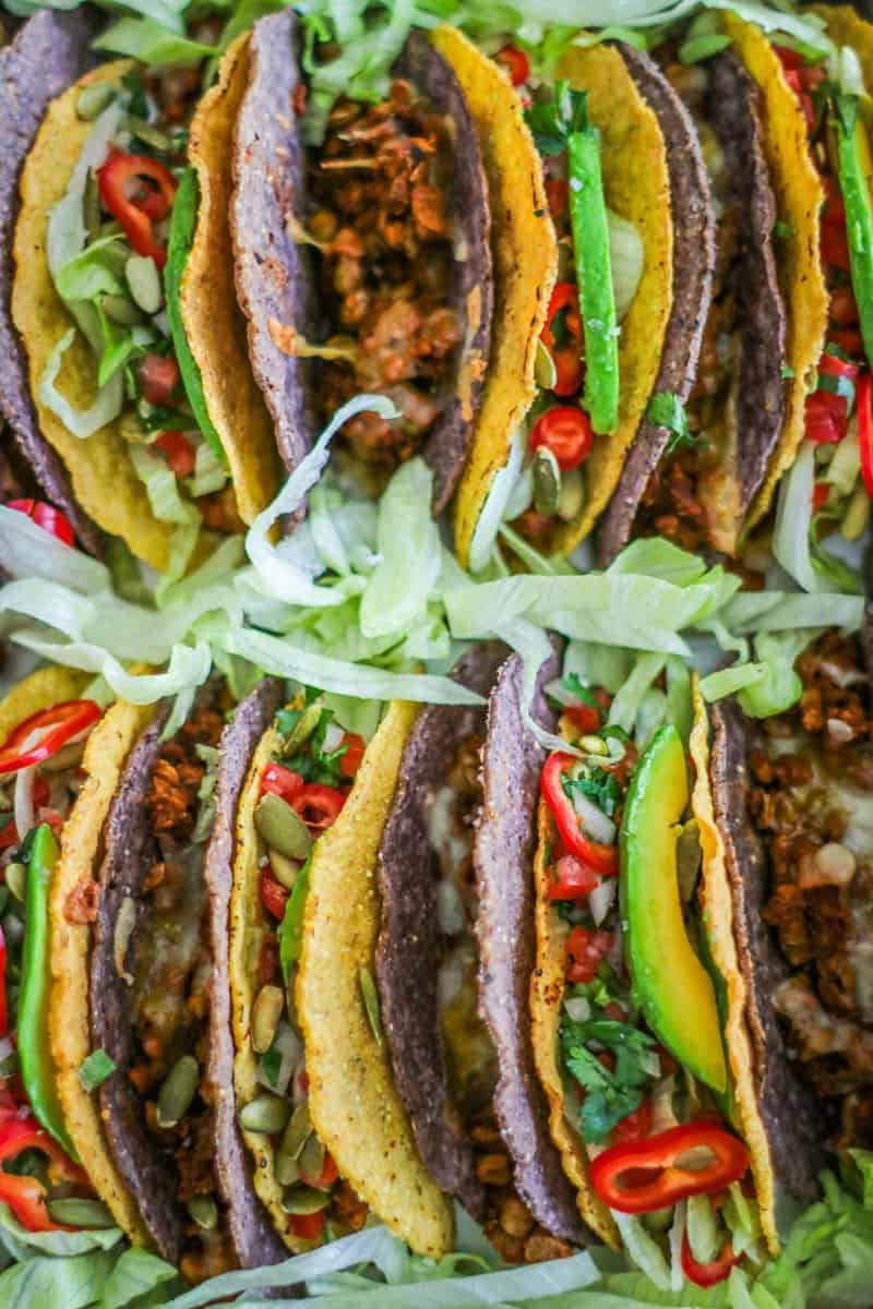 close up of Baking pan filled with tacos made of lentils and meatless beef crumbles topped with lettuce, pico de gallo, peppers, avocado slices, and pepitas