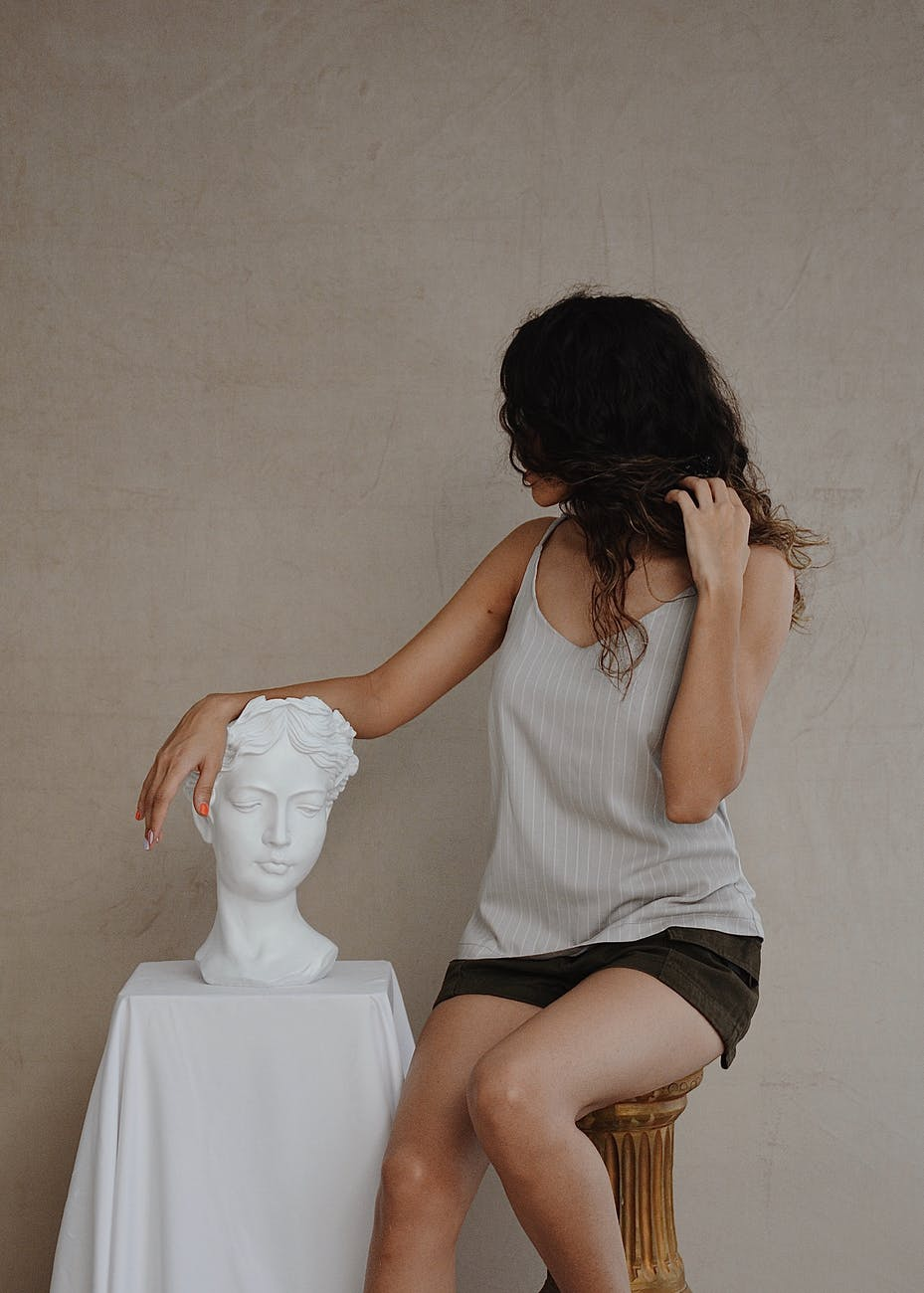 anonymous woman in trendy outfit near stone bust