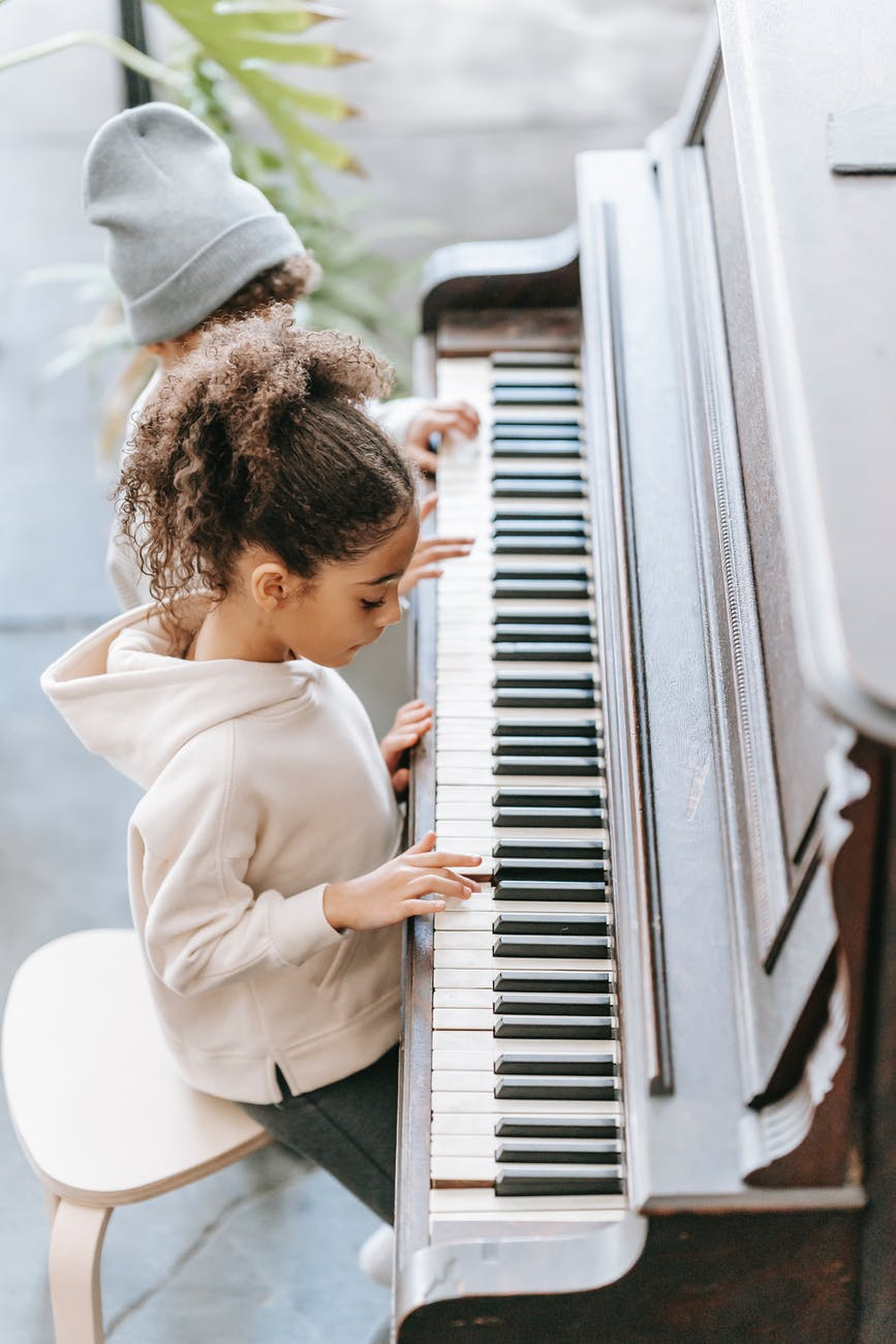 focused ethnic kid playing piano with sibling at home