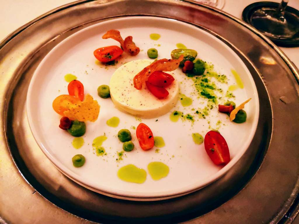 Flan di formaggio caprino alle erbe accompagnato da pomodorini, finferli e pane di Lagundo