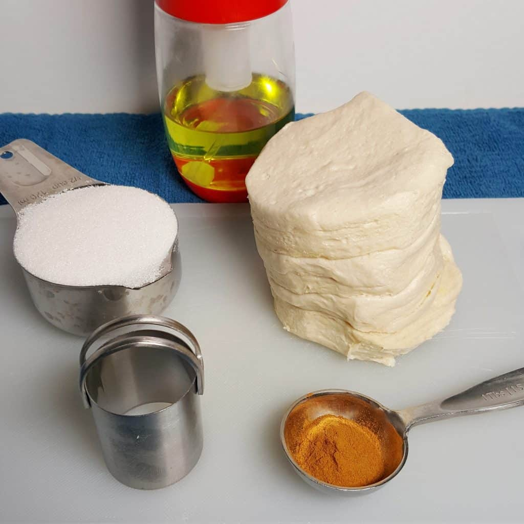Ingredients, refrigerator biscuits, cinnamon, sugar, biscuit cutter and oil mister