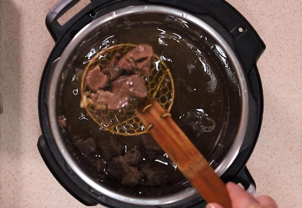 Remove the meat from cooking pot and place into barbecue sauce