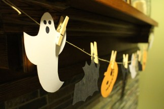Paper ghosts, jack-o-lanterns, bats and black cats in a simple paper banner
