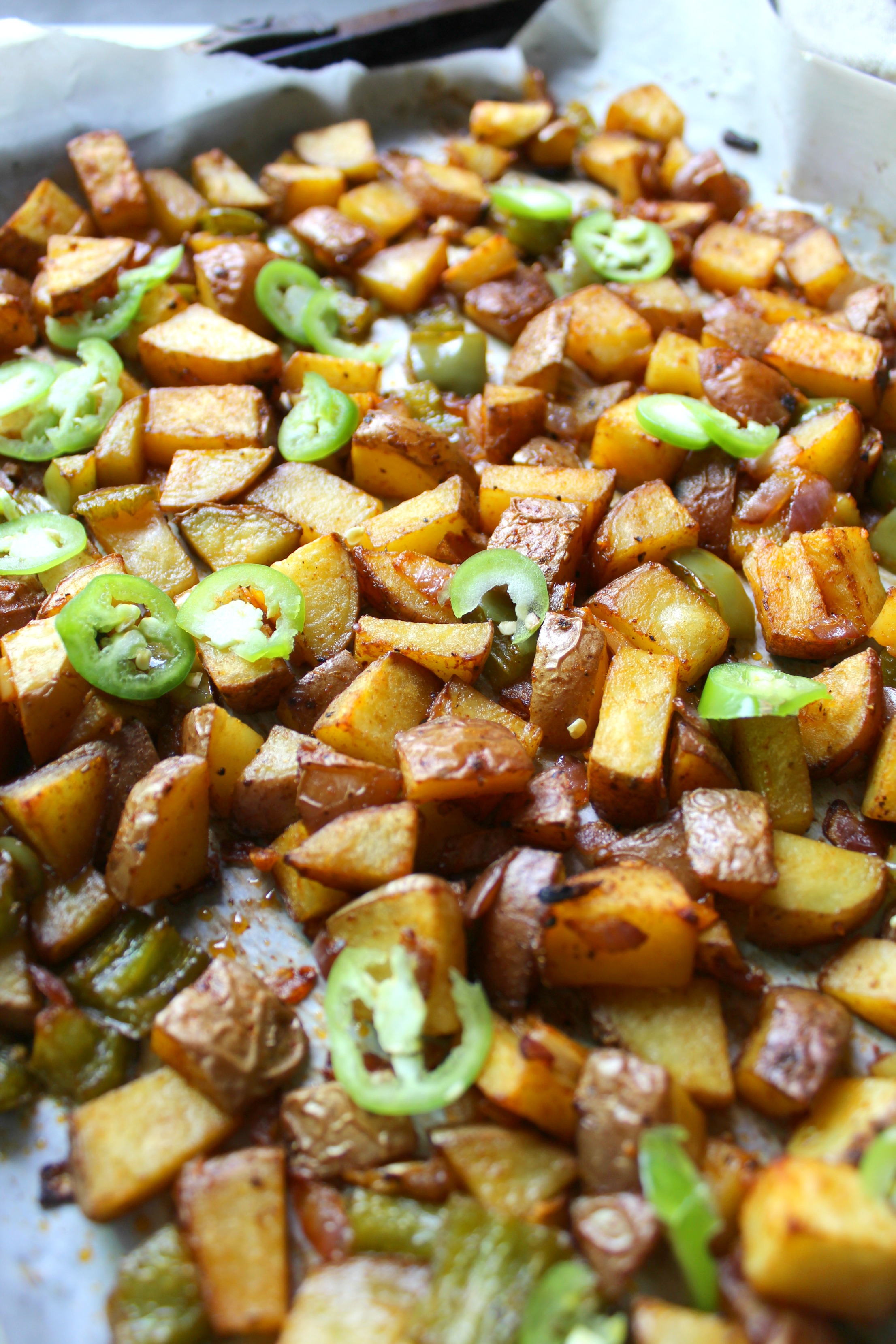 Spice up breakfast with these Sheet Pan Breakfast Potatoes. Cooked with bell peppers, onions and serrano peppers in vegan butter until crisped to perfection!   ThisSavoryVegan.com