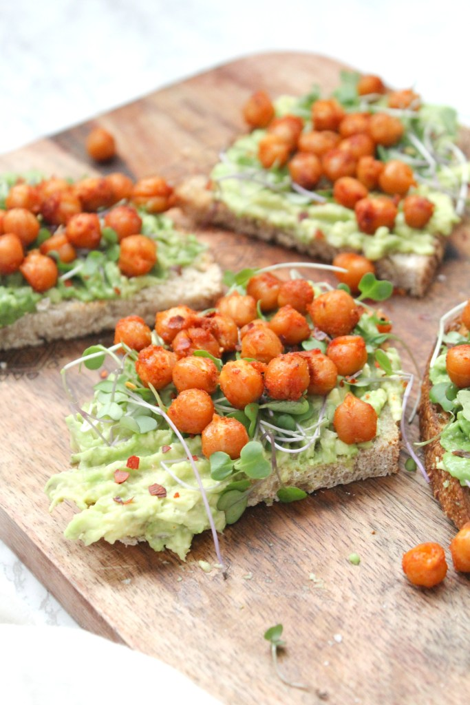 This Roasted Chickpea Avocado Toast steps up the classic vegan breakfast. Toasted bread is topped with smashed avocados, smoky chickpeas and sprouts   ThisSavoryVegan.com #thissavoryvegan #avocadotoast