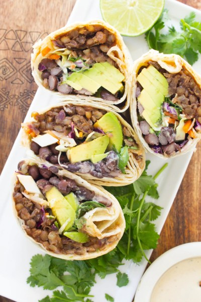 These Vegan BBQ Lentil Burritos are loaded with black beans, tangy slaw, avocado, BBQ lentils and a creamy tahini dressing | ThisSavoryVegan.com #thissavoryvegan #vegan #veganburritos