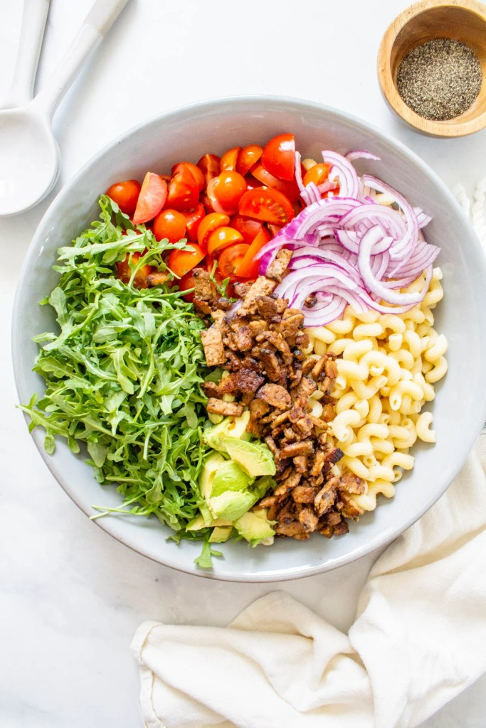 This Vegan BLT Pasta Salad is perfect for a summer BBQ! It is loaded with tempeh bacon, cherry tomatoes, arugula, avocado, red onion and a creamy dressing | ThisSavoryVegan.com #thissavoryvegan #veganpastasalad #veganbbq