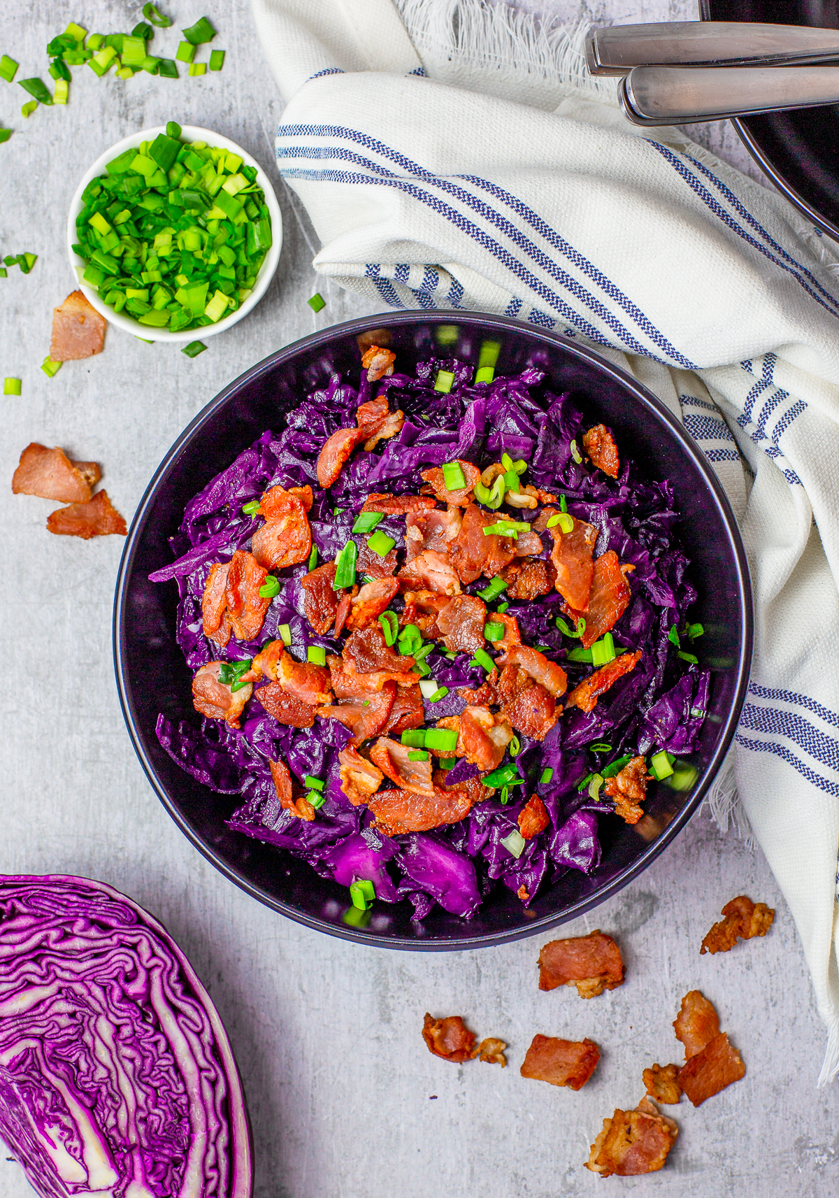 Overhead photo of Sweet and Sour Cabbage in bowl with bacon and scallionns.