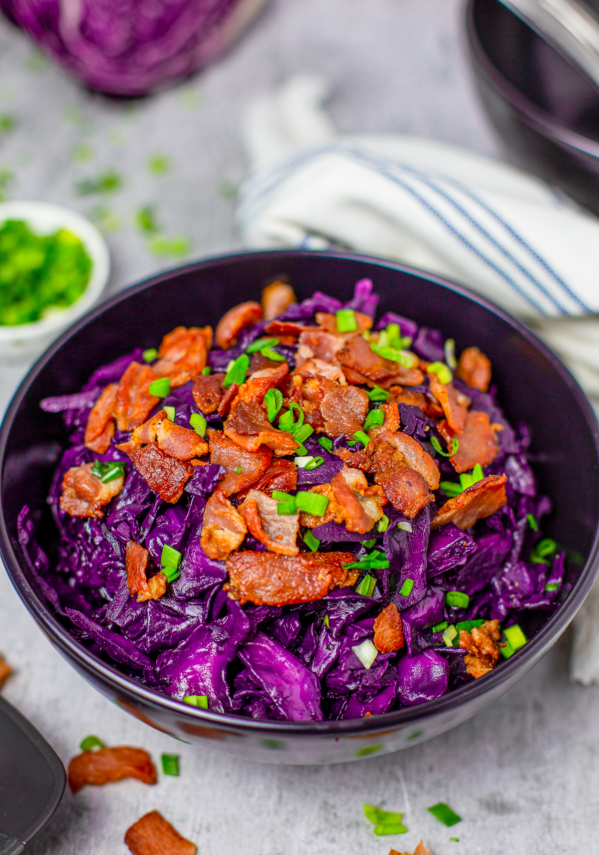Close up of Sweet and Sour Cabbage Recipe in bowl topped with bacon and scallionos.