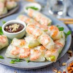Square image of Salad Rolls layered on plate with dipping sauce